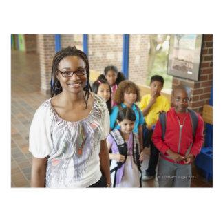 Teacher and students in school hallway postcard