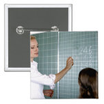 teacher and young girl in front of blackboard in button