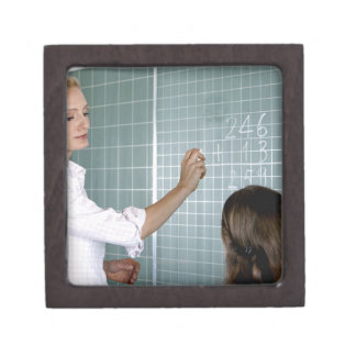 teacher and young girl in front of blackboard in jewelry box