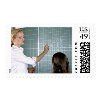 teacher and young girl in front of blackboard in postage
