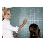 teacher and young girl in front of blackboard in postcard