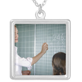 teacher and young girl in front of blackboard in silver plated necklace