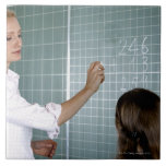 teacher and young girl in front of blackboard in large square tile