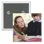 teacher assisting child with work in classroom buttons