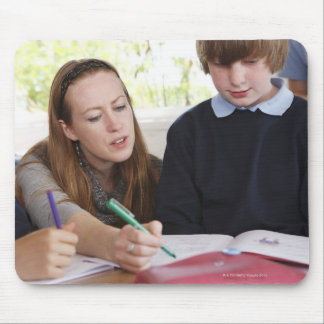 teacher assisting child with work in classroom mouse pad