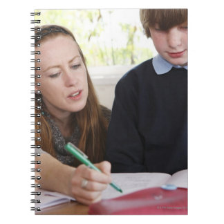 teacher assisting child with work in classroom spiral notebook