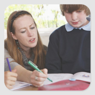 teacher assisting child with work in classroom square sticker