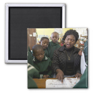 Teacher assists a group of learner's in the magnet