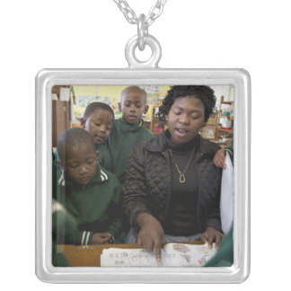 Teacher assists a group of learner's in the silver plated necklace