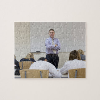 Teacher at front of class, children working hard jigsaw puzzle
