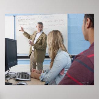 Teacher at whiteboard explaining lesson to poster
