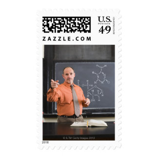 Teacher by chalkboard with structure of chemical stamps