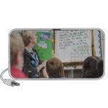 Teacher giving classroom presentation to laptop speakers