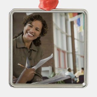 Teacher giving paperwork to student metal ornament
