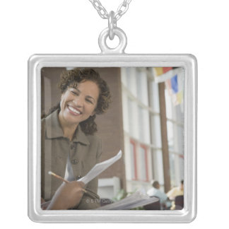 Teacher giving paperwork to student silver plated necklace