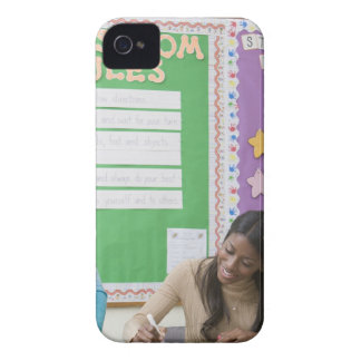 Teacher grading girls paper in classroom iPhone 4 cover