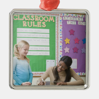 Teacher grading girls paper in classroom metal ornament