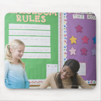 Teacher grading girls paper in classroom mouse pad