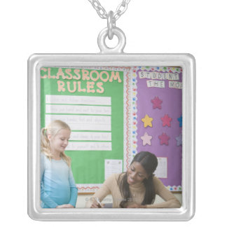 Teacher grading girls paper in classroom pendant