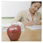 Teacher grading papers with apple in foreground ceramic tile