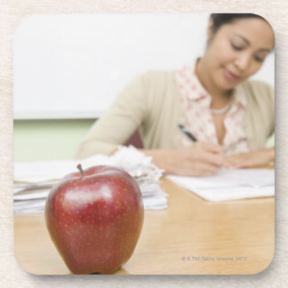 Teacher grading papers with apple in foreground drink coaster