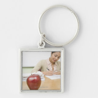 Teacher grading papers with apple in foreground keychain