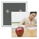 Teacher grading papers with apple in foreground pinback button