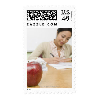 Teacher grading papers with apple in foreground stamps