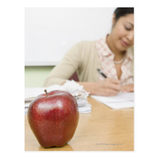 Teacher grading papers with apple in foreground postcard