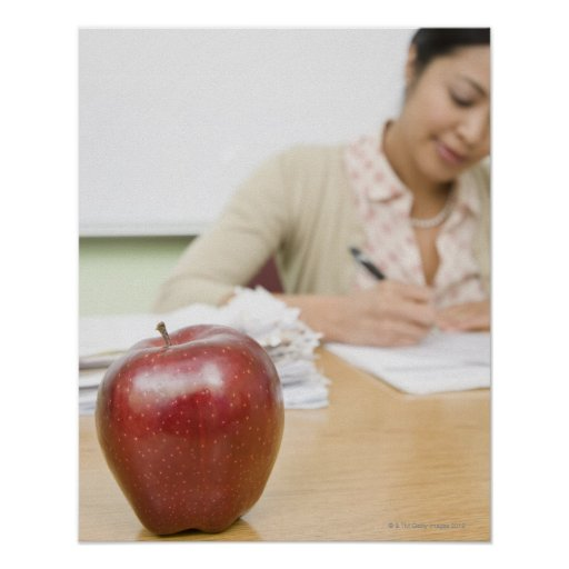 Teacher grading papers with apple in foreground poster