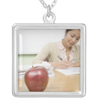 Teacher grading papers with apple in foreground square pendant necklace