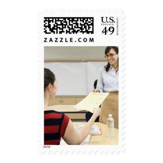 Teacher handing paper back to student postage