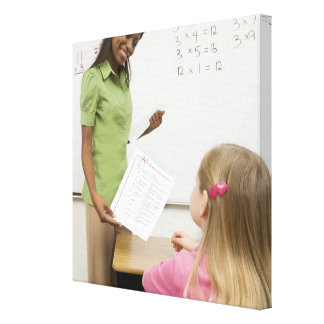 Teacher handing paper to student with A plus Canvas Print