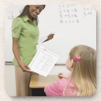 Teacher handing paper to student with A plus Coaster