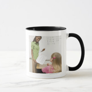 Teacher handing paper to student with A plus Mug