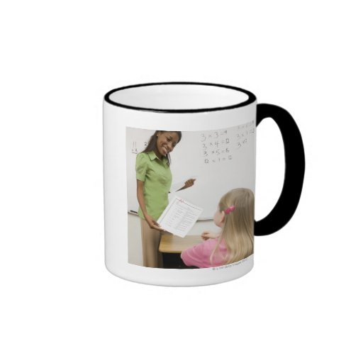 Teacher handing paper to student with A plus Coffee Mugs