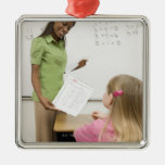 Teacher handing paper to student with A plus Ornaments