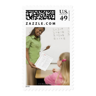 Teacher handing paper to student with A plus Postage Stamp