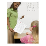 Teacher handing paper to student with A plus Post Card