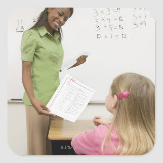 Teacher handing paper to student with A plus Square Sticker
