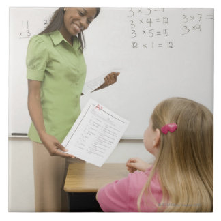 Teacher handing paper to student with A plus Tile