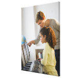 Teacher helping student in computer lab canvas print