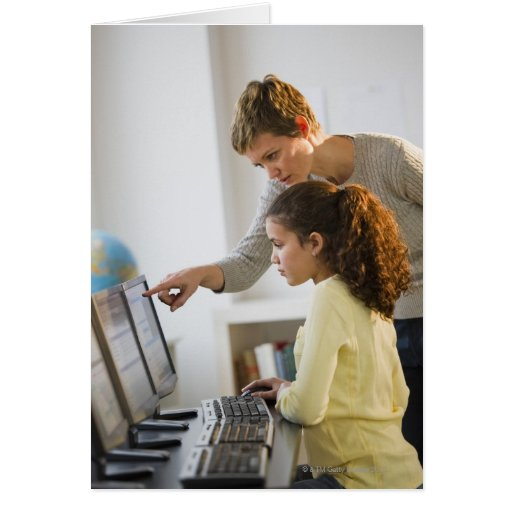 Teacher helping student in computer lab greeting cards
