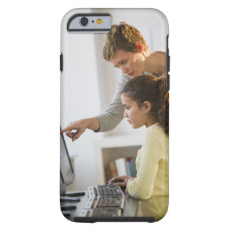 Teacher helping student in computer lab tough iPhone 6 case