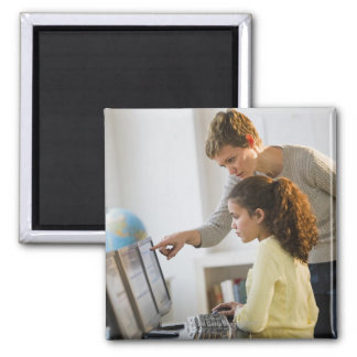 Teacher helping student in computer lab magnet