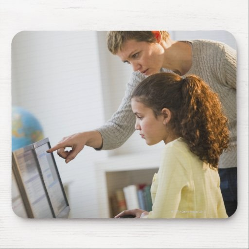 Teacher helping student in computer lab mouse pad