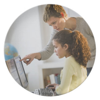 Teacher helping student in computer lab party plates