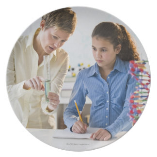 Teacher helping student in science lab dinner plate