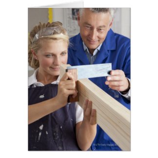 Teacher helping student measuring planed wood in card