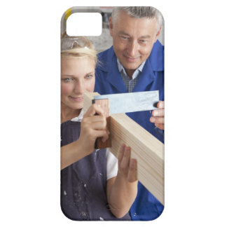 Teacher helping student measuring planed wood in iPhone 5 cover